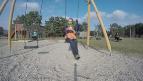 Mother with baby daughter girl swing in park playground. 4K stock video footage