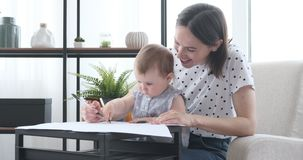 Mother with baby daughter learning to draw on paper stock footage