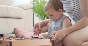 Mother with baby daughter playing foosball. Mother with baby daughter learning to play foosball at home stock video footage