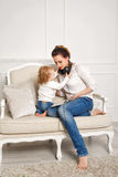 Mother and baby daughter. Listen to music Royalty Free Stock Photos