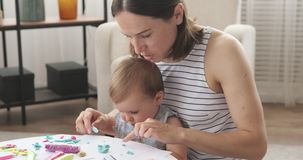 Mother and little daughter playing with plasticine stock footage