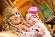 Mother with baby daughter on merry-go-round. Beautiful young mother with baby daughter taking a ride on traditional Parisian merry-go-round stock photos