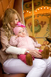 Mother with baby daughter on merry-go-round Royalty Free Stock Photography
