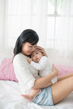 Mother and baby daughter plays, hugging, kissing at home on bed royalty free stock photography