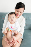 Mother and baby daughter plays, hugging, kissing at home on the Royalty Free Stock Photo