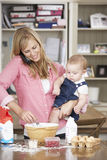Mother And Baby Daughter Preparing Ingredients To Bake Cakes In Kitchen Stock Photos
