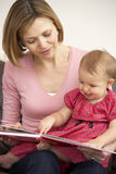 Mother And Baby Daughter Reading Book. Together Stock Photography