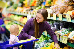 Mother and baby daughter in supermarket Royalty Free Stock Images