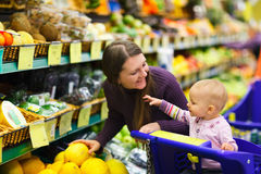Mother and baby daughter in supermarket Royalty Free Stock Photos