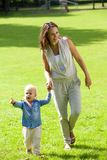 Mother and baby daughter walking outdoors royalty free stock photos