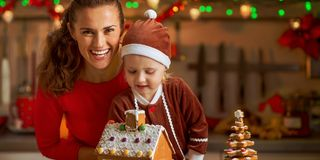 Mother and baby decorating christmas cookie house in kit Royalty Free Stock Photos