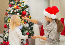 Mother and baby decorating Christmas tree Royalty Free Stock Image