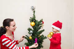 Mother with baby decorating the Christmas tree Royalty Free Stock Photo