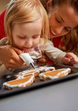 Mother and baby decorating homemade christmas cookies Stock Images