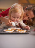 Mother and baby decorating homemade christmas cookies with glaze Stock Photography