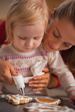 Mother and baby decorating homemade christmas cookies with glaze Stock Images