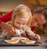 Mother and baby decorating homemade christmas cookies with glaze Stock Photo