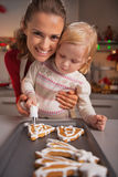 Mother and baby decorating homemade christmas cookies with glaze Stock Image