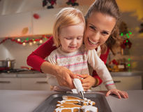 Mother and baby decorating homemade cookies with glaze Stock Image