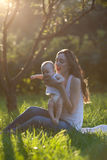 Mother and baby doing exercise routine outdoors Royalty Free Stock Photos