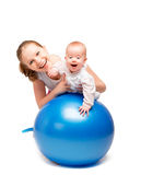 Mother and baby doing gymnastic exercises on the ball Stock Photos