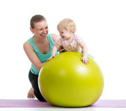 Mother with baby doing gymnastic on fitness ball. Mother doing gymnastics with baby on fitness ball Royalty Free Stock Images
