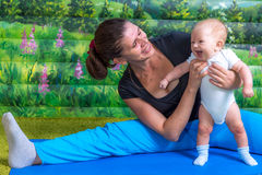 Mother with baby doing gymnastics. Fun mood Stock Image
