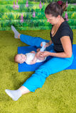 Mother with baby doing gymnastics. Fun mood Royalty Free Stock Photography
