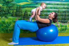 Mother with baby doing gymnastics. Mom does gymnastics with the child. Fun mood Stock Images