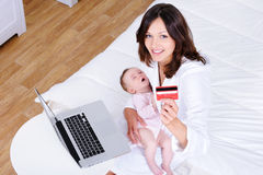 Mother with baby doing internet shopping stock image