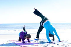Mother and baby doing yoga. Baby and mother doing yoga on the beach Royalty Free Stock Photo