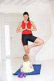 Mother and baby doing yoga. In home gym Royalty Free Stock Images