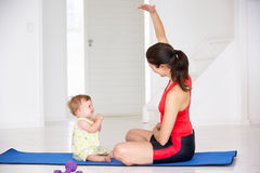 Mother and baby doing yoga together. On yoga mat at home Royalty Free Stock Photo