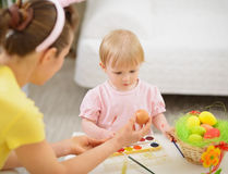 Mother and baby drawing on Easter eggs Royalty Free Stock Photos
