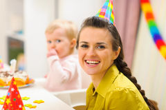 Mother and baby eating birthday cake in background Royalty Free Stock Image