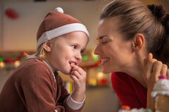 Mother and baby eating christmas snacks in kitchen Stock Images