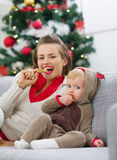 Mother and baby eating cookies near Christmas tree Royalty Free Stock Image