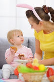 Mother with baby eating Easter cookies Stock Photography