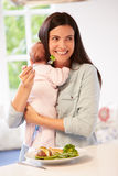 Mother With Baby Eating Healthy Meal In Kitchen Stock Photography