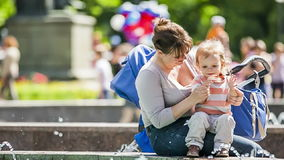 Mother And Baby Enjoying Fountains In The Park Stock Photo