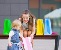 Mother and baby examines purchases after shopping Stock Photography