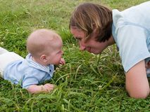 Mother and baby face-to-face. Family of mother and baby playing together face-to-face on the grass meadow in holiday vacations Stock Images