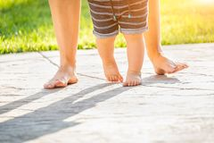 Mother and Baby`s Feet Taking Steps Outdoors stock images