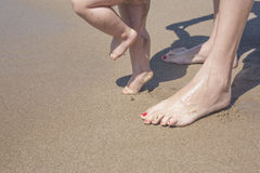 Mother and baby feet walking on sand beach Stock Photo