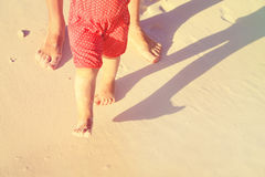 Mother and baby feet walking on sand beach Royalty Free Stock Image