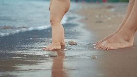 Mother and baby foot walking on sand beach. Newborn kid feet at beach. Mother and baby foot walking on sand beach. Close up of newborn kid feet at beach. Mom stock footage