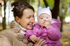 Mother and baby in forest. Mother holding a baby with a bagel in the autumn forest stock photo