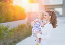 Mother and baby in front of house building looking on copy space. Happy mother and baby in front of house building looking on copy space royalty free stock photo
