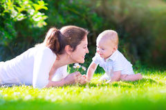 Mother and baby in the garden. Happy beautiful woman, young mother playing with her adorable baby son, cute little boy, enjoying together a sunny warm day Stock Image