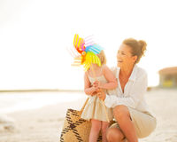 Mother and baby girl behind colorful windmill toy Royalty Free Stock Photo